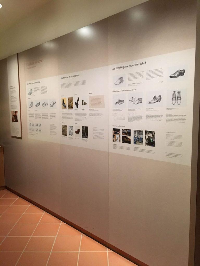 Drei zum Teil bedruckte Holzwände in einer Ausstellung