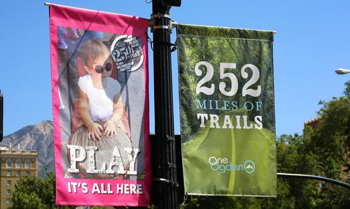 Zwei kleine Banner an Auslegern an einer Straßenlaterne