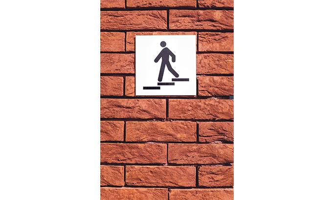 Schild mit Treppensymbol auf einer Backsteinwand