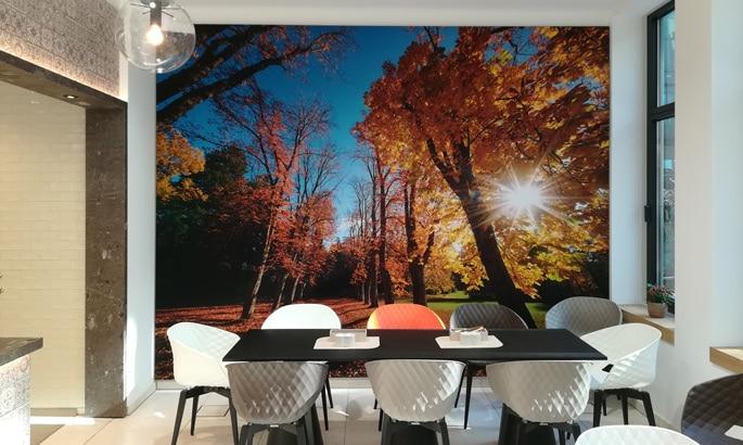 Großes Bild an der Wand mit Waldmotiv im Vordergrund Stühle