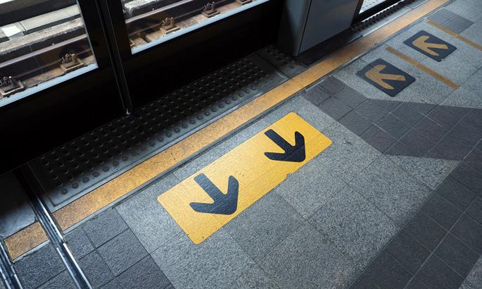 Folien in gelb mit schwarzen Pfeilen an einer U-Bahn Haltestelle