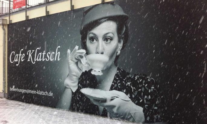Fassadenbanner aus PVC mit einer Frau, die Kaffee trinkt an einer Fassade