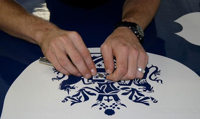 Ein Werbetechniker entgittern ein feinteiliges wappenähnliches blaues Logo