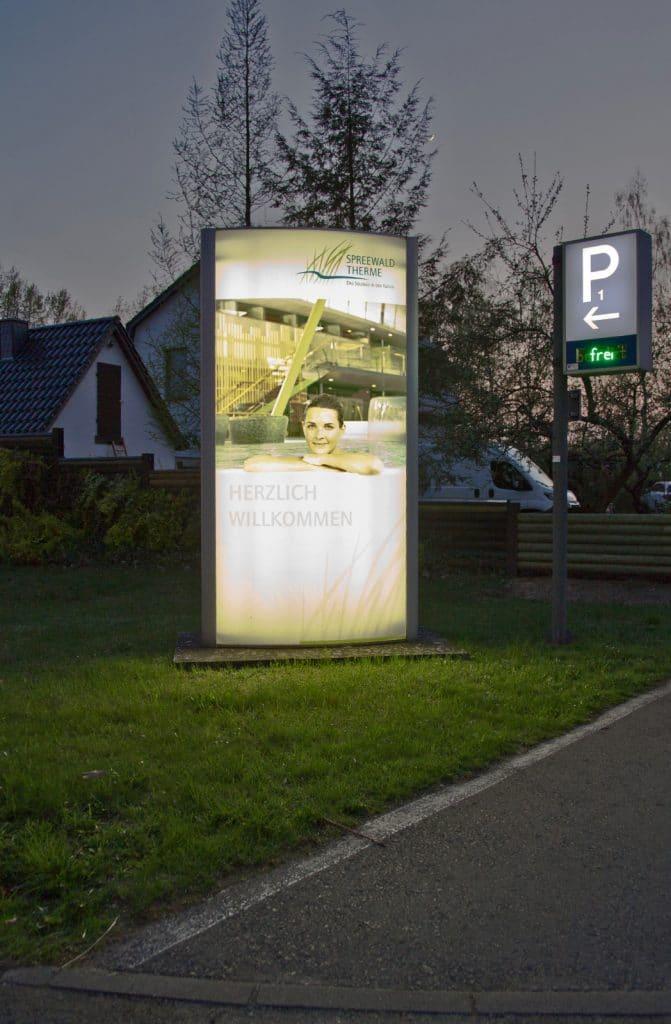 Beleuchteter Pylon mit Firmenwerbung