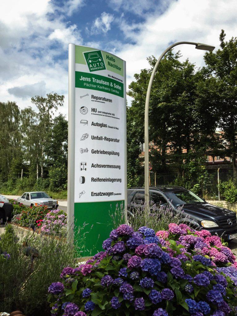Großer, grün-weißer Firmenpylon im Außenbereich an einem Parkplatz