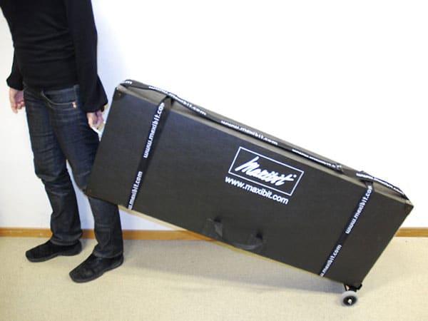 Mann mit einer schwarzen Transportbox mit Rollen