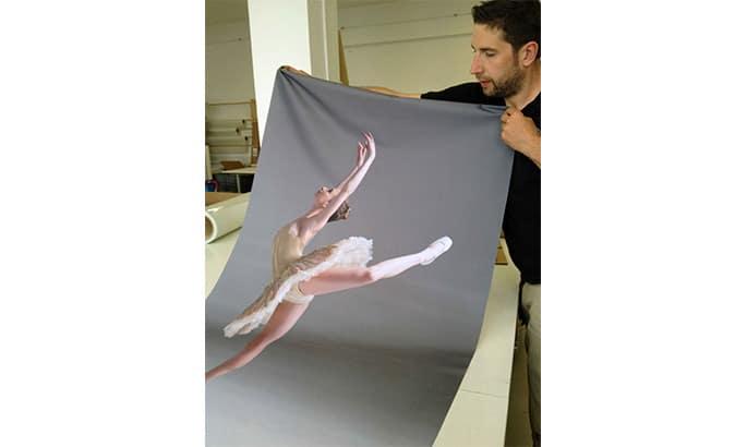 Mann hält einen mit einer Balletttänzerin bedruckten Stoff hoch