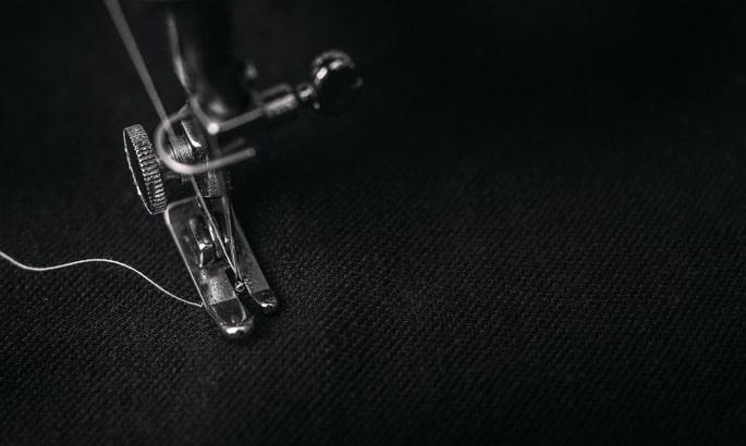 Kopf einer Nähmaschine, die schwarzen Stoff näht