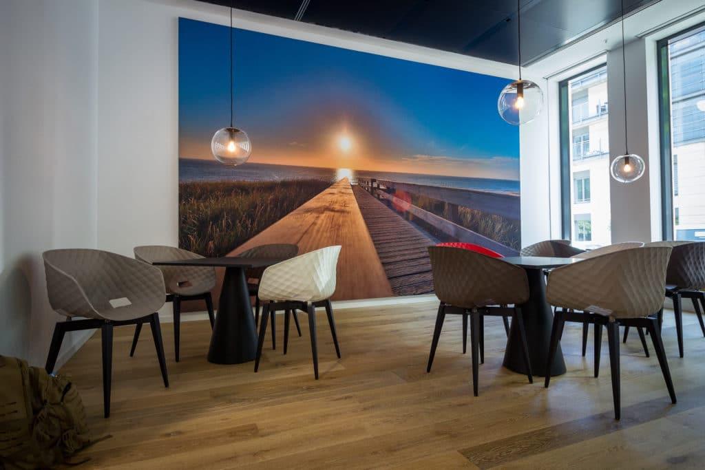 großes stoffbild mit strandmotivin einem aluspannrahmen an der wand in einer kantine mit bunten stühlen