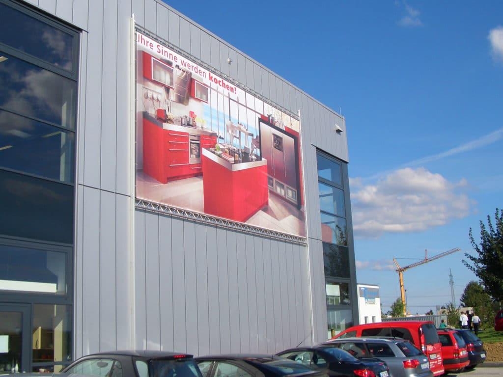 Liftsystem mit einem Großformatbanner an einer Fassade eines Möbelhauses