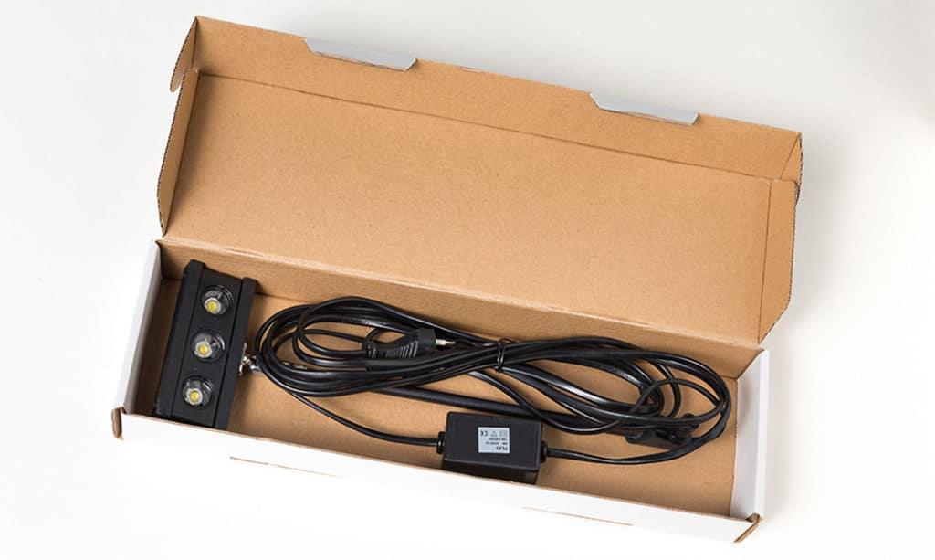 Verpackungskarton mit einer schwarzen LED Bannerleuchte