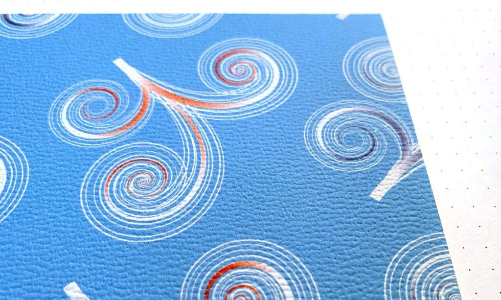 Detail einer geprägten Tapete mit Kringeln auf blauem Grund