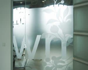 glasdekor intarsien mit Text und Blumenmotiv an einer Glasscheibe