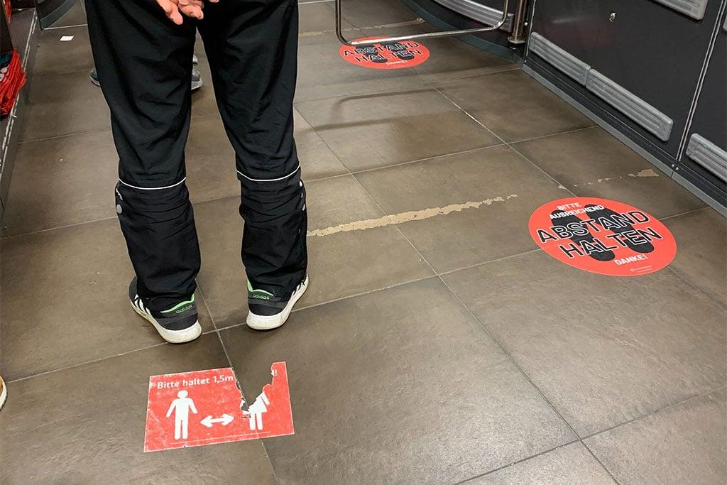 Markierung mit Fußbodenfolie zum Abstand halten Kassenbereich eines Supermarktes