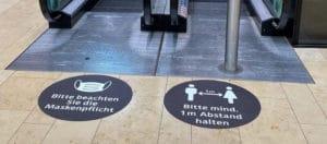Zwei Fußbodenfolien vor einer Rolltreppe